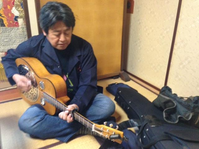 三吉神社社務所内の控え室で。この日入手した新しいドブロを試奏。
